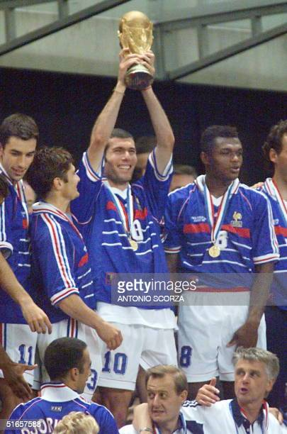 French midfielder Zinedine Zidane holds up the FIFA World Cup Trophy as Robert Pires Bixente Lizarazu and Marcel Desailly smile 12 July at the Stade...