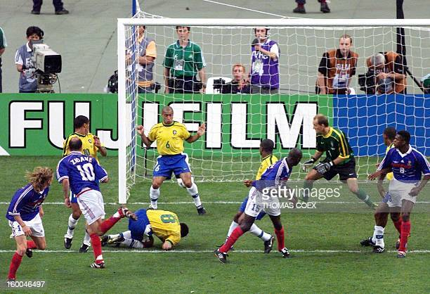 French midfielder Zinedine Zidane watch his header go through the legs of Brazilian defender Roberto Carlos for his second goal of the game as...
