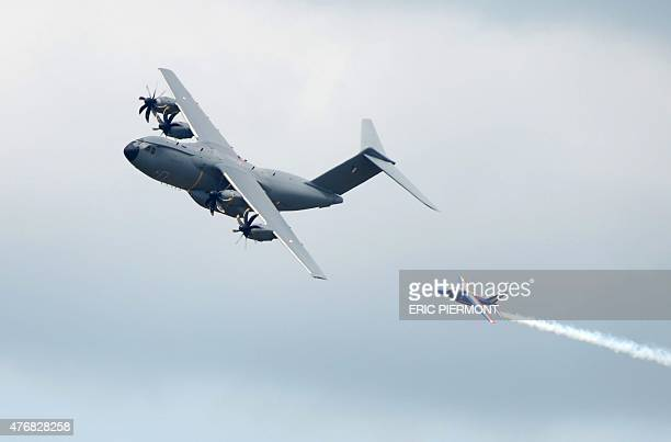 A French military Airbus A400M flies next to French elite acrobatic flying team 'Patrouille de France' Alphajet on June 12 2015 during the flight...
