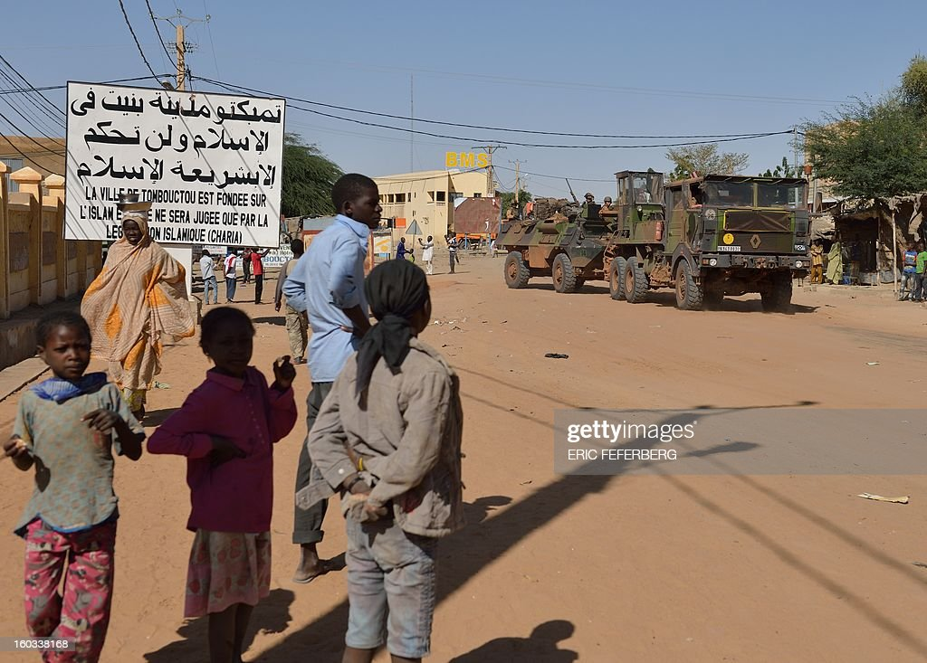 A French military convoy crosses on January 29, 2013 Timbuktu after French-led troops freed the northern desert city on January 28 from Islamist control. Hundreds of Malians looted Arab-owned shops on January 29 in Timbuktu as global donors pledged over 455 million US dollars (340 million euro) at a donor conference in the Ethiopian capital Addis Ababa for military operations in Mali and humanitarian aid to rout the radicals from the north. Sign reads 'The city of Timbuktu is founded on Islam and will be judged only by the Islamic law (sharia)). AFP PHOTO / ERIC FEFERBERG