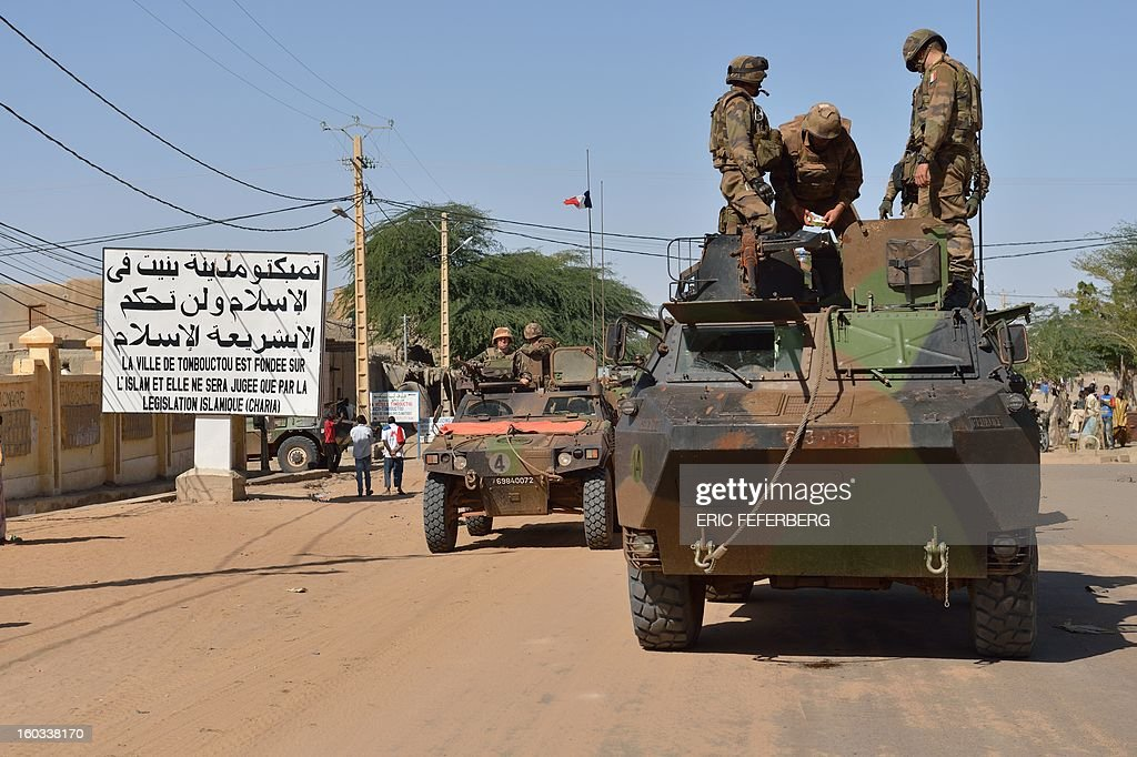 A French military convoy crosses on January 29, 2013 Timbuktu after French-led troops freed the northern desert city on January 28 from Islamist control. Hundreds of Malians looted Arab-owned shops on January 29 in Timbuktu as global donors pledged over 455 million US dollars (340 million euro) at a donor conference in the Ethiopian capital Addis Ababa for military operations in Mali and humanitarian aid to rout the radicals from the north. Sign reads 'The city of Timbuktu is founded on Islam and will be judged only by the Islamic law (sharia)).