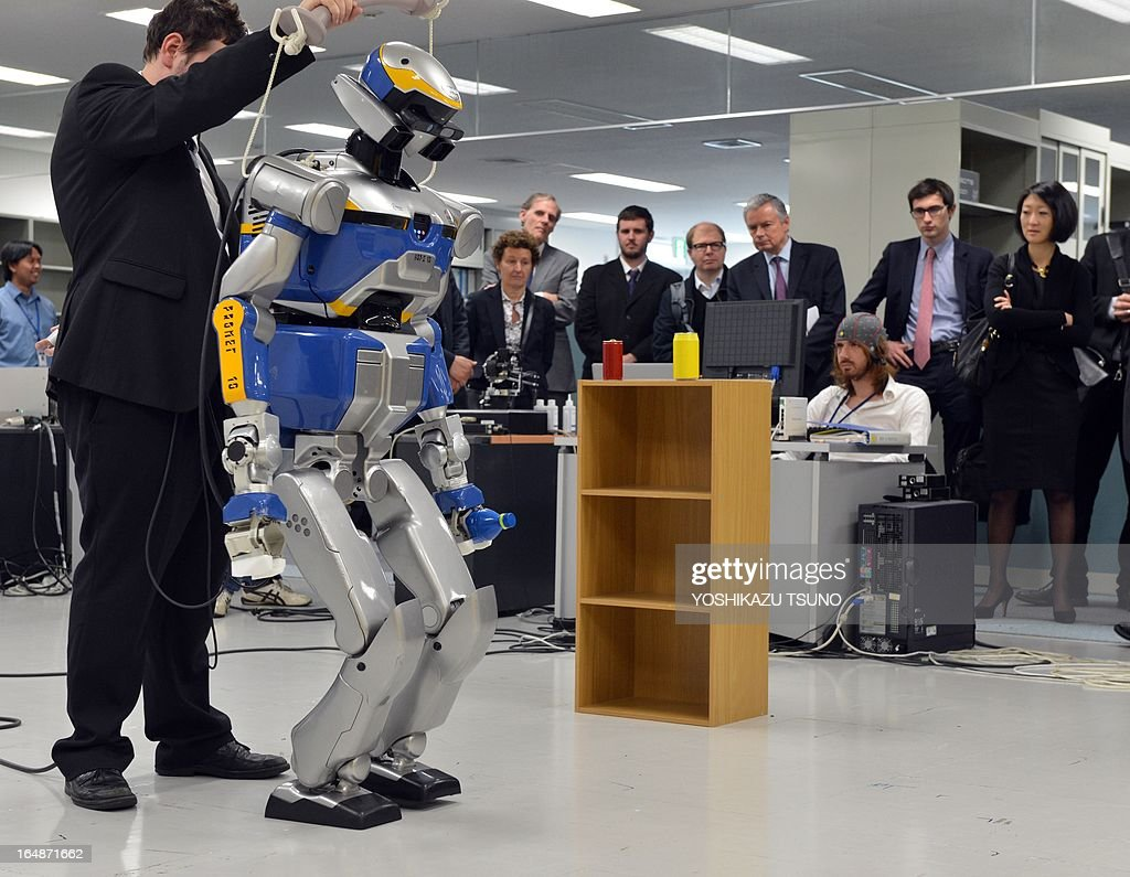 French Minister Fleur Pellerin (R) inspects a demonstration of a humanoid robot HRP-2, which is controlled by human brain activity with the brain machine interface (BMI) in the Japan-France joint laboratory at the National Institute of Advanced Industrial Science and Technology (AIST)in Tsukuba, suburban Tokyo on March 29, 2013. The HAL, which is designed to learn the user's motion and assist the wearer's movement, can be used for the rehabilitation of disabled and assist elderly people. AFP PHOTO / Yoshikazu TSUNO