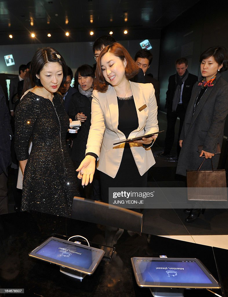 French Minister Fleur Pellerin (L) is shown around a showroom of Samsung Electronics in Seoul on March 26, 2013. Pellerin, the junior minister for small and medium enterprises, innovation and the digital economy, began a highly anticipated visit on March 23 to South Korea, the land of her birth, where her unusual success story is a source of public pride, admiration and curiosity. AFP PHOTO / JUNG YEON-JE