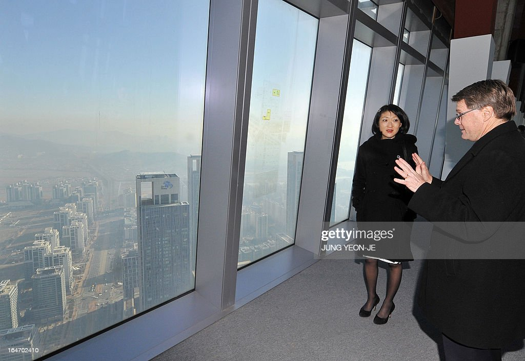 French Minister Fleur Pellerin (2nd R) listens to Scatt Summers (R), vice president of Gale Internaional, in the sky lounge of Northeast Asia Trade Center at the Songdo International Business District in Incheon, west of Seoul, on March 27, 2013. Pellerin, the junior minister for small and medium enterprises, innovation and the digital economy, began a highly anticipated visit on March 23 to South Korea, the land of her birth, where her unusual success story is a source of public pride, admiration and curiosity.