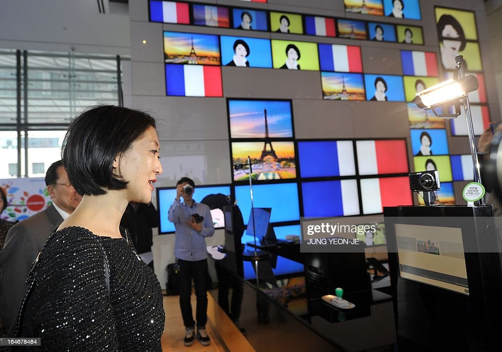 French Minister Fleur Pellerin (L) looks around a showroom of Samsung Electronics in Seoul on March 26, 2013. Pellerin, the junior minister for small and medium enterprises, innovation and the digital economy, began a highly anticipated visit on March 23 to South Korea, the land of her birth, where her unusual success story is a source of public pride, admiration and curiosity. AFP PHOTO / JUNG YEON-JE