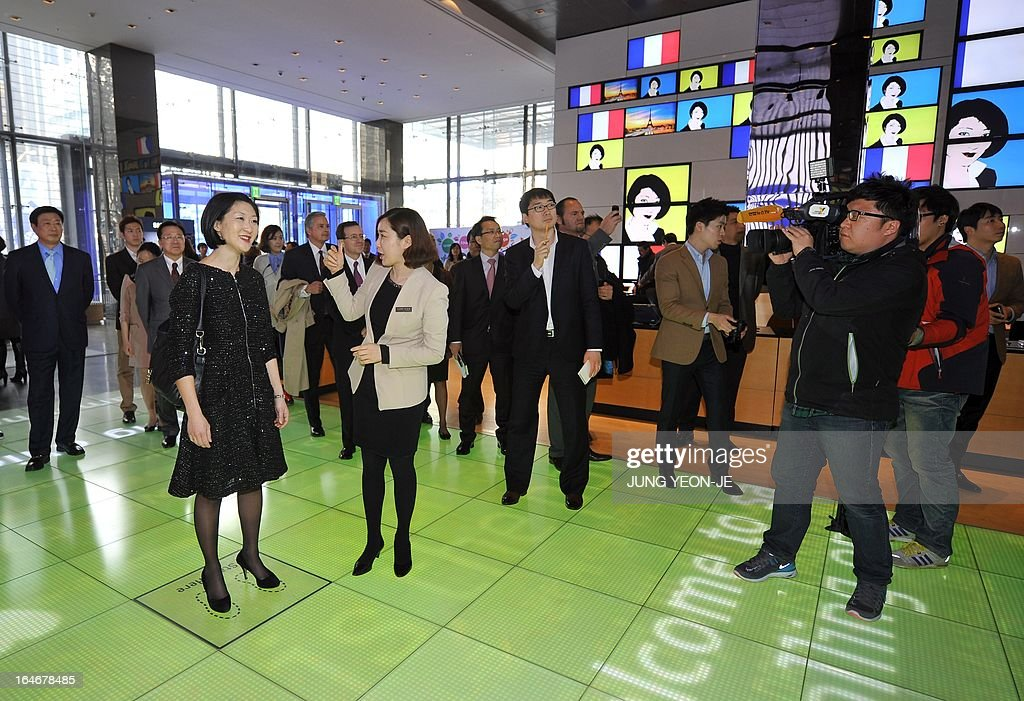 French Minister Fleur Pellerin (front L) looks around a showroom of Samsung Electronics in Seoul on March 26, 2013. Pellerin, the junior minister for small and medium enterprises, innovation and the digital economy, began a highly anticipated visit on March 23 to South Korea, the land of her birth, where her unusual success story is a source of public pride, admiration and curiosity.