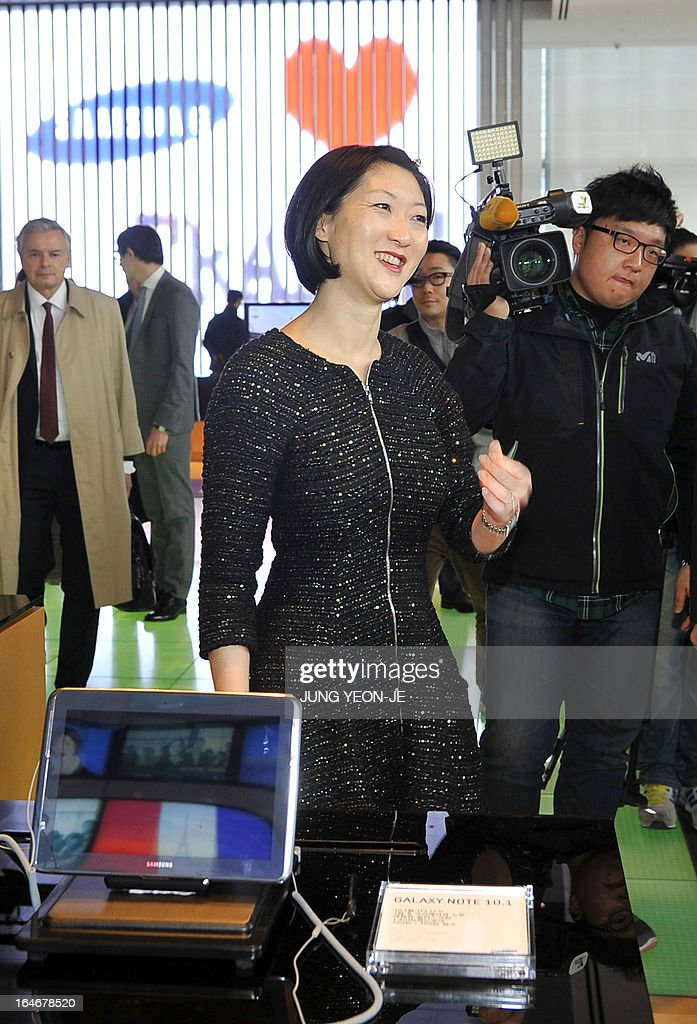 French Minister Fleur Pellerin (C) looks around a showroom of Samsung Electronics in Seoul on March 26, 2013. Pellerin, the junior minister for small and medium enterprises, innovation and the digital economy, began a highly anticipated visit on March 23 to South Korea, the land of her birth, where her unusual success story is a source of public pride, admiration and curiosity.