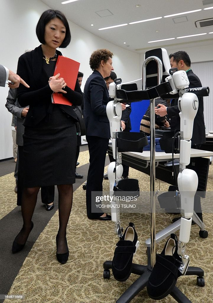 French Minister Fleur Pellerin looks at a robot suit, Hybrid Assistive Limb (HAL), developed by University of Tsukuba professor Yoshiyuki Sankai at his company Cyberdyne in Tsukuba, suburban Tokyo on March 29, 2013. The HAL, which is designed to learn the user's motion and assist the wearer's movement, can be used for the rehabilitation of disabled and assist elderly people. AFP PHOTO / Yoshikazu TSUNO