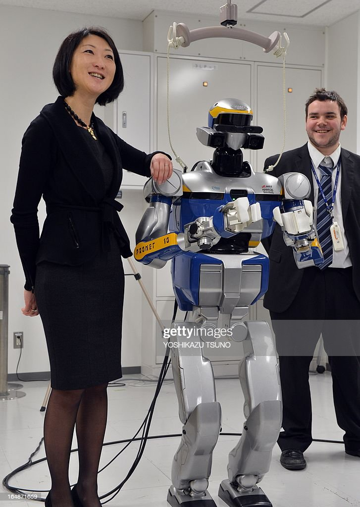 French Minister Fleur Pellerin (L) smiles as she inspects a demonstration of a humanoid robot HRP-2, which is controled by human brain activity with the brain machine interface (BMI) in the Japan-France joint laboratory at the National Institute of Advanced Industrial Science and Technology (AIST) in Tsukuba, suburban Tokyo on March 29, 2013. The HAL, which is designed to learn the user's motion and assist the wearer's movement, can be used for the rehabilitation of disabled and assist elderly people. AFP PHOTO / Yoshikazu TSUNO