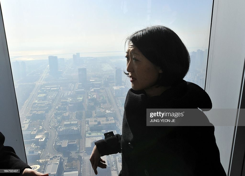 French Minister Fleur Pellerin walks by a window in the sky lounge of Northeast Asia Trade Center at the Songdo International Business District in Incheon, west of Seoul, on March 27, 2013. Pellerin, the junior minister for small and medium enterprises, innovation and the digital economy, began a highly anticipated visit on March 23 to South Korea, the land of her birth, where her unusual success story is a source of public pride, admiration and curiosity. AFP PHOTO / JUNG YEON-JE