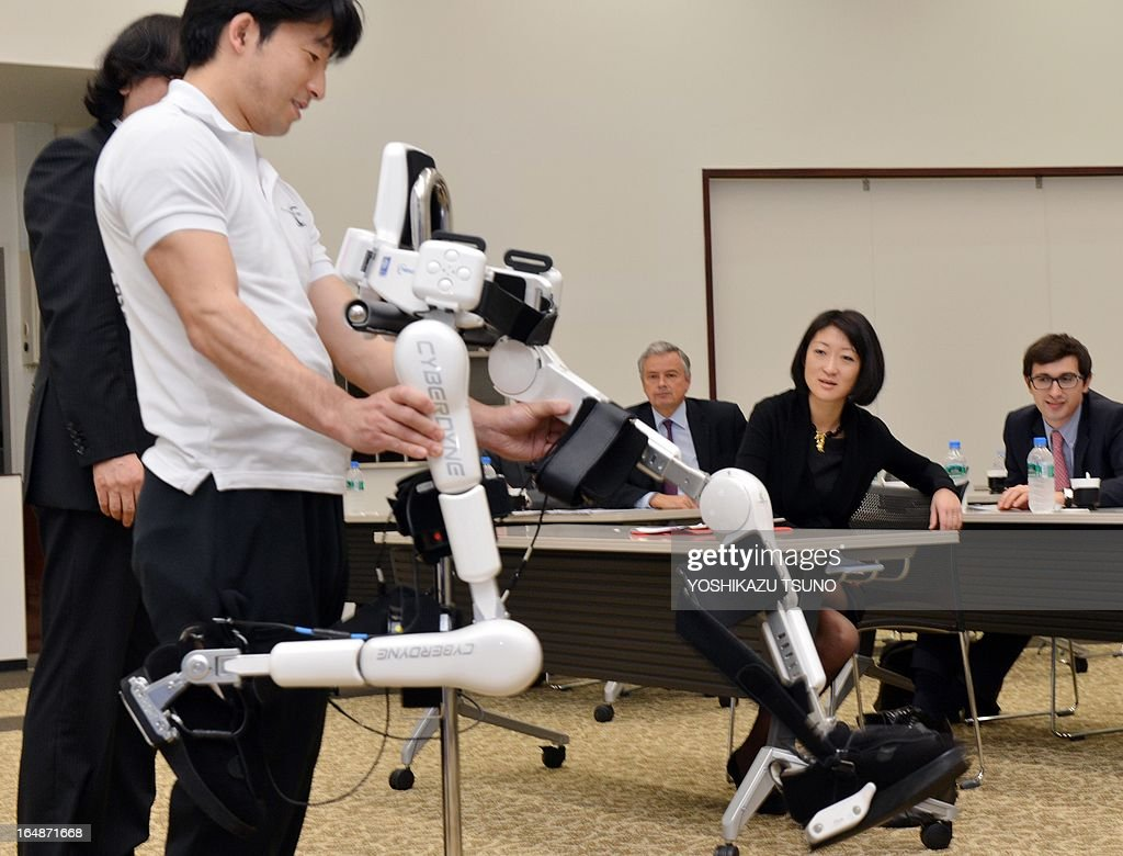French Minister Fleur Pellerin (2nd R) watches a demonstration of a robot suit, Hybrid Assistive Limb (HAL), developed by University of Tsukuba professor Yoshiyuki Sankai at his company Cyberdyne in Tsukuba, suburban Tokyo on March 29, 2013. The HAL, which is designed to learn the user's motion and assist the wearer's movement, can be used for the rehabilitation of disabled and assist elderly people. AFP PHOTO / Yoshikazu TSUNO