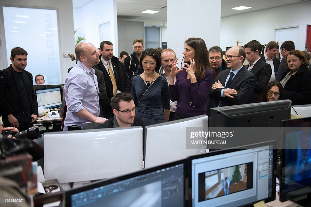 French Minister for Culture and Communication Aurelie Filippetti (C, right) and Junior Minister in charge of small and medium enterprises and the digital economy Fleur Pellerin (C) speak with David Cage (L), founder and president of Quantic Dream, during a visit of the headquarters of the French video game company on April 4, 2013 in Paris.
