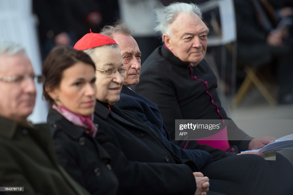 French Minister for Culture and Communication Aurelie Filippetti, French archbishop Andre Vingt-Trois, Paris' mayor Bertrand Delanoe and Patrick Jacquin, the head priest and rector of the Notre-Dame de Paris cathedral, listen the ringing of the new bells of Notre Dame Cathedral in Paris on March 23, 2013, as part of the formal inauguration.