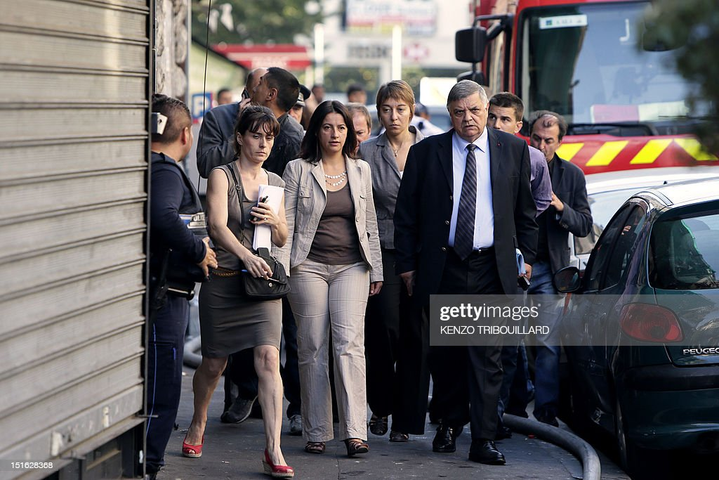 French Minister for Equality of Territories and Housing, Cecile Duflot (CL) and Seine-Saint-Denis' prefect Christian Lambert (CR) arrive on the scene of a fire on September 9, 2012 in Saint-Denis, near Paris. Two people died, four were seriously injured and eleven have been slightly injured in the fire, of undetermined origin, that broke out in an habitation building in the center of Saint-Denis during the night from Saturday to Sunday. AFP PHOTO KENZO TRIBOUILLARD