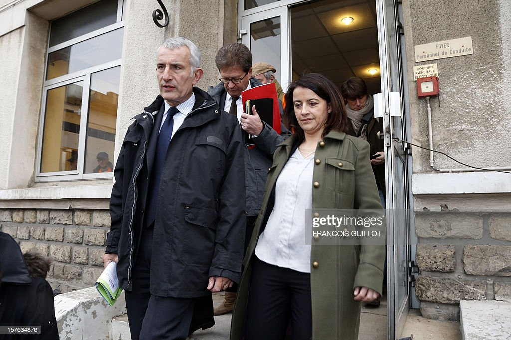 French Minister for Equality of Territories and Housing Cecile Duflot (R) and France national rail company SNCF head, Guillaume Pepy (L) leave after visiting a building belonging to French railway company SNCF and which will be used as temporary housing for homeless on December 5, 2012 in Ivry-sur-Seine.