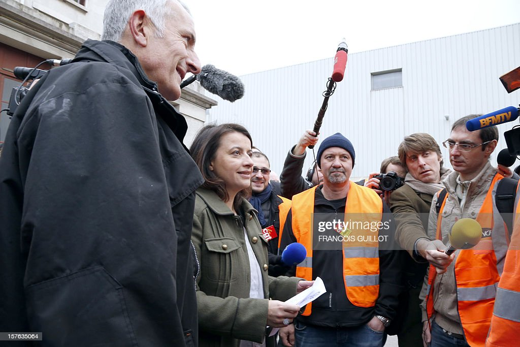 French Minister for Equality of Territories and Housing Cecile Duflot (2ndL) and France national rail company SNCF head, Guillaume Pepy speak with railworkers after visiting a building belonging to French railway company SNCF and which will be used as temporary housing for homeless on December 5, 2012 in Ivry-sur-Seine.