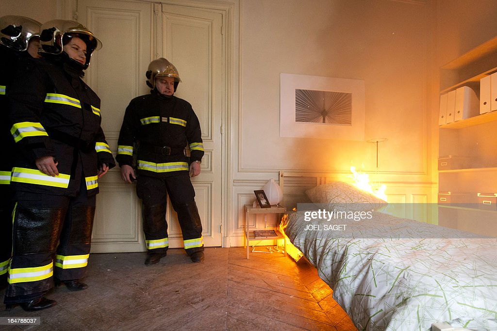 French Minister for Equality of Territories and Housing Cecile Duflot (2ndL) takes part in a firefighting exercise on March 28, 2013 in Paris, focused on benefits of smoke detectors.