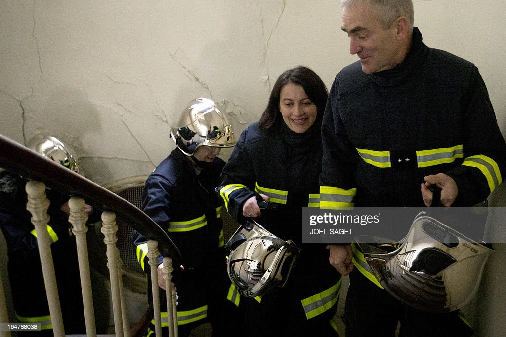 French Minister for Equality of Territories and Housing Cecile Duflot (C) takes part in a firefighting exercise on March 28, 2013 in Paris, focused on benefits of smoke detectors.