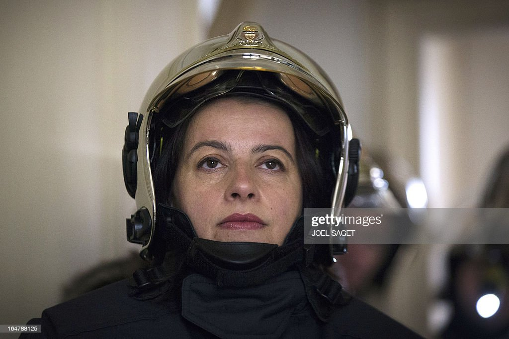 French Minister for Equality of Territories and Housing Cecile Duflot takes part in a firefighting exercise on March 28, 2013 in Paris, focused on benefits of smoke detectors. AFP PHOTO / JOEL SAGET