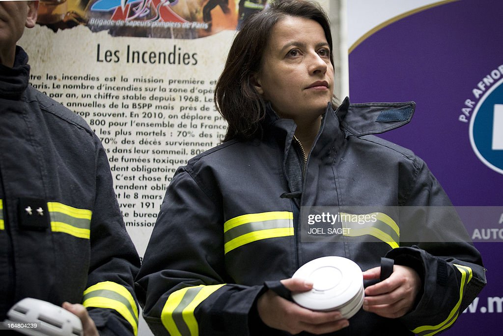 French Minister for Equality of Territories and Housing Cecile Duflot holds a smoke detector in her hands during a test organised by French firefighters to outline the benefits of smoke detectors, on March 28, 2013 in Paris.
