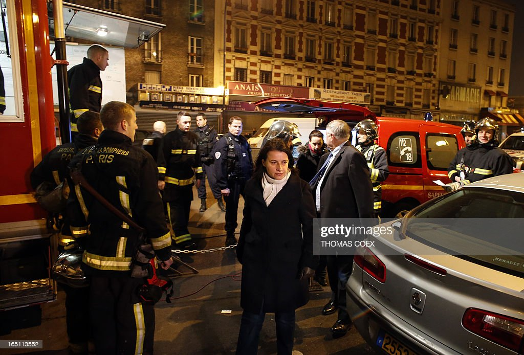 French Minister for Equality of Territories and Housing Cecile Duflot (C) arrives at the site of a building that was gutted by fire in Aubervilliers, a suburb of Paris, on March 30, 2013. Two people were killed and five others were seriously injured in the fire.