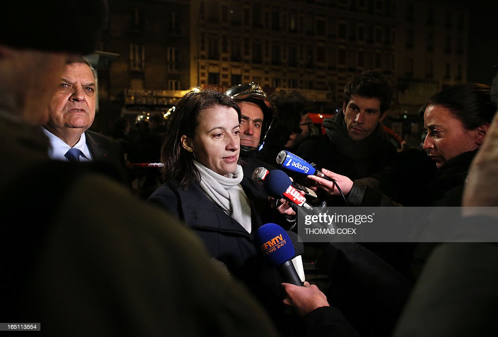 French Minister for Equality of Territories and Housing Cecile Duflot (C) talks to journalists as she arrives at the site of a building that was gutted by fire in Aubervilliers, a suburb of Paris, on March 30, 2013. Two people were killed and five others were seriously injured in the fire.