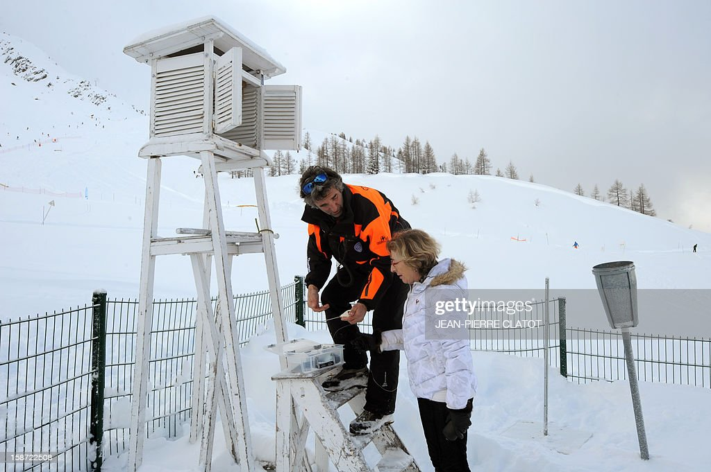 French Minister for Higher Education and Research, Genevieve Fioraso, listens to a man as she looks an altitude weather station, near Les Grand Montets' pistes, in Chamonix, French Alps, on December 26, 2012 as part of a visit focused on research on global warming and the risk of avalanches. AFP PHOTO / JEAN-PIERRE CLATOT