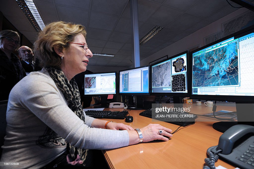 French Minister for Higher Education and Research, Genevieve Fioraso, (L) looks at screens at the weather station of Chamonix, French Alps, on December 26, 2012 as part of a visit focused on research on global warming and the risk of avalanches. AFP PHOTO / JEAN-PIERRE CLATOT