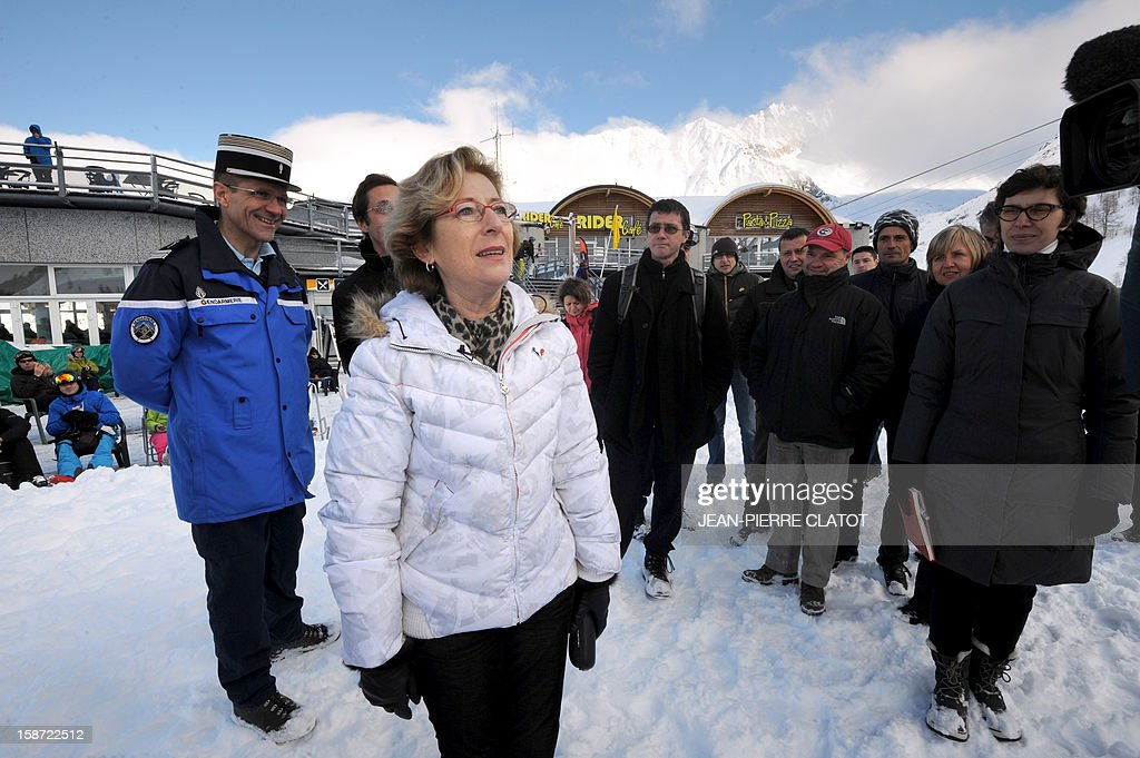 French Minister for Higher Education and Research, Genevieve Fioraso, (2ndL) walks near Les Grand Montets' pistes, to visit an altitude weather station, in Chamonix, French Alps, on December 26, 2012 as part of a visit focused on research on global warming and the risk of avalanches.