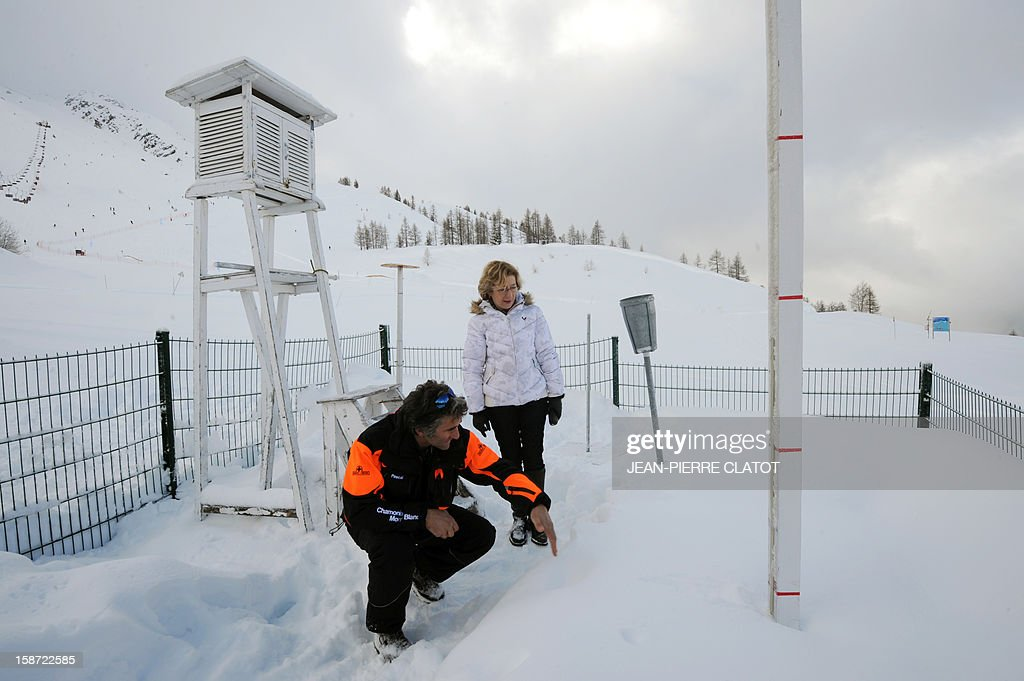 French Minister for Higher Education and Research, Genevieve Fioraso, listens to a man in front of an altitude weather station, near Les Grand Montets' pistes, in Chamonix, French Alps, on December 26, 2012 as part of a visit focused on research on global warming and the risk of avalanches.