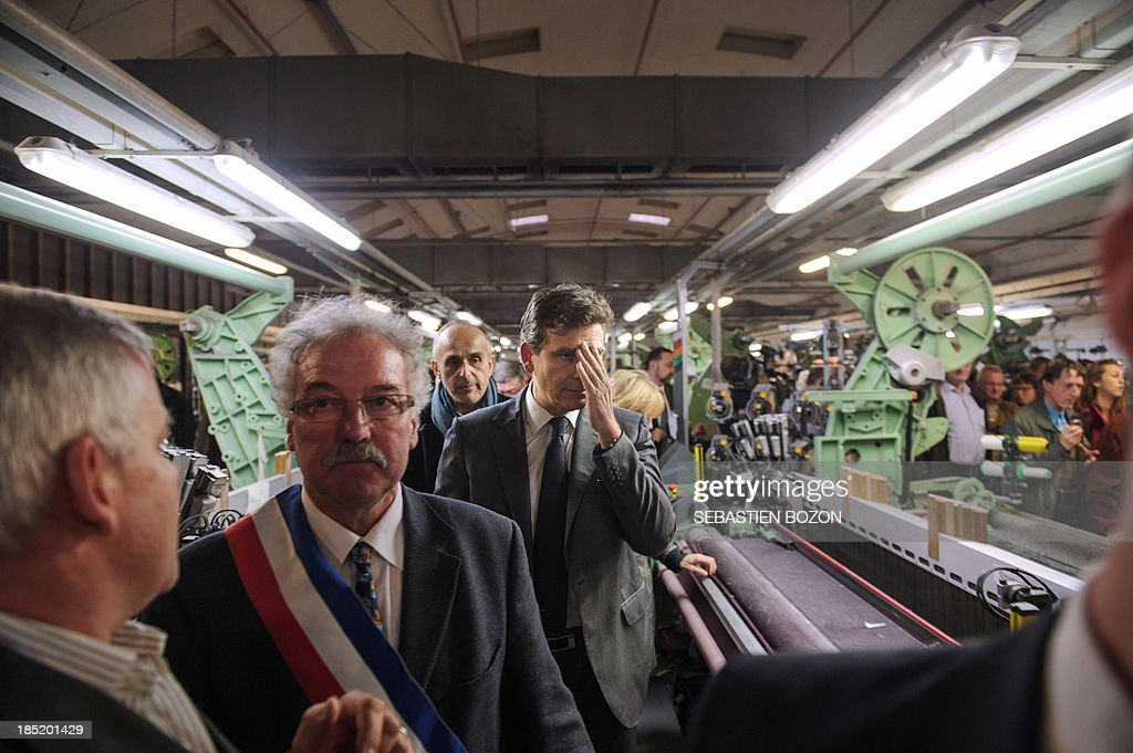 French minister for Industrial Recovery and Food Industry Arnaud Montebourg (C) visits the Virtuose textile factory which is already into liquidation on October 18, 2013 in Hirsingue, eastern France.