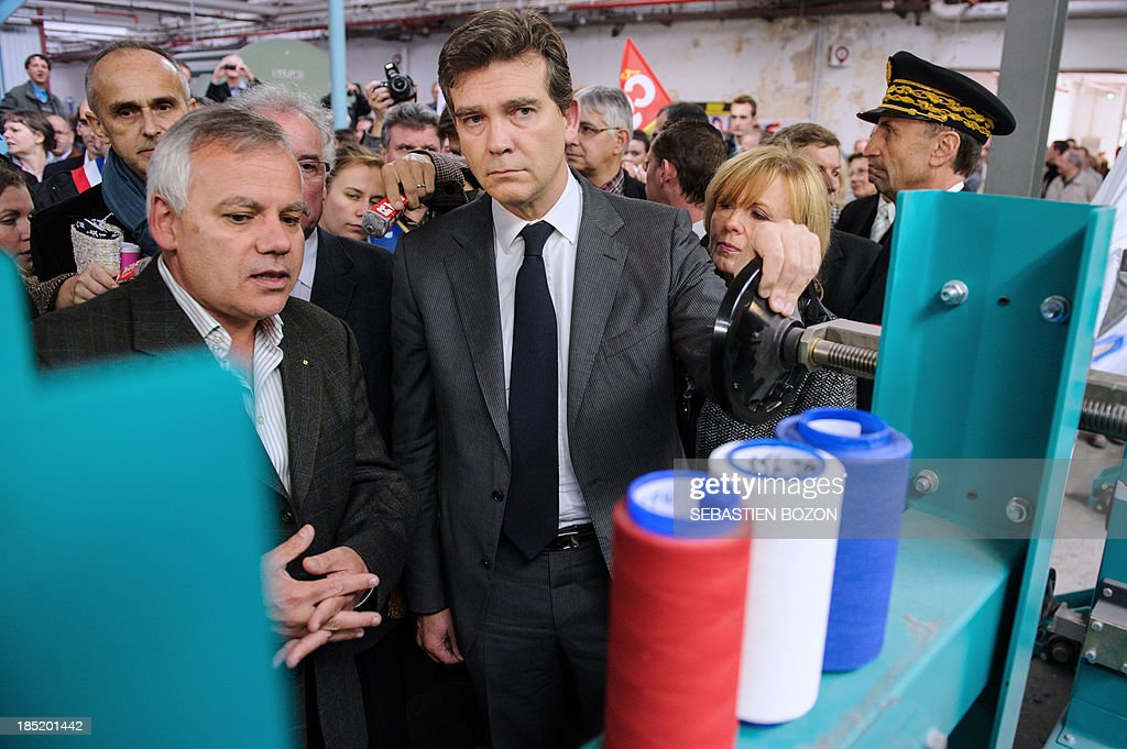 French minister for Industrial Recovery and Food Industry Arnaud Montebourg (C) speaks with Christian Didier (L), one of the two potential buyers of the Virtuose textile factory which is already into liquidation, during a visit in Hirsingue, eastern France,on October 18, 2013.