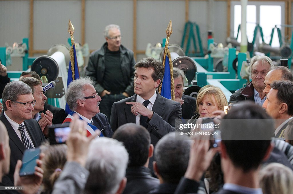 French minister for Industrial Recovery and Food Industry Arnaud Montebourg (C) speaks with Hirsingue mayor Armand Reinhard (2ndL) during a visit of the Virtuose textile factory which is already into liquidation, in Hirsingue, eastern France, on October 18, 2013.