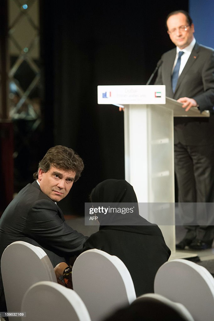 French Minister for Industrial Recovery Arnaud Montebourg (L) attends the press conference of French President Francois Hollande (back) at the World Future Energy Summit (WFES) in Dubai on January 15, 2013.