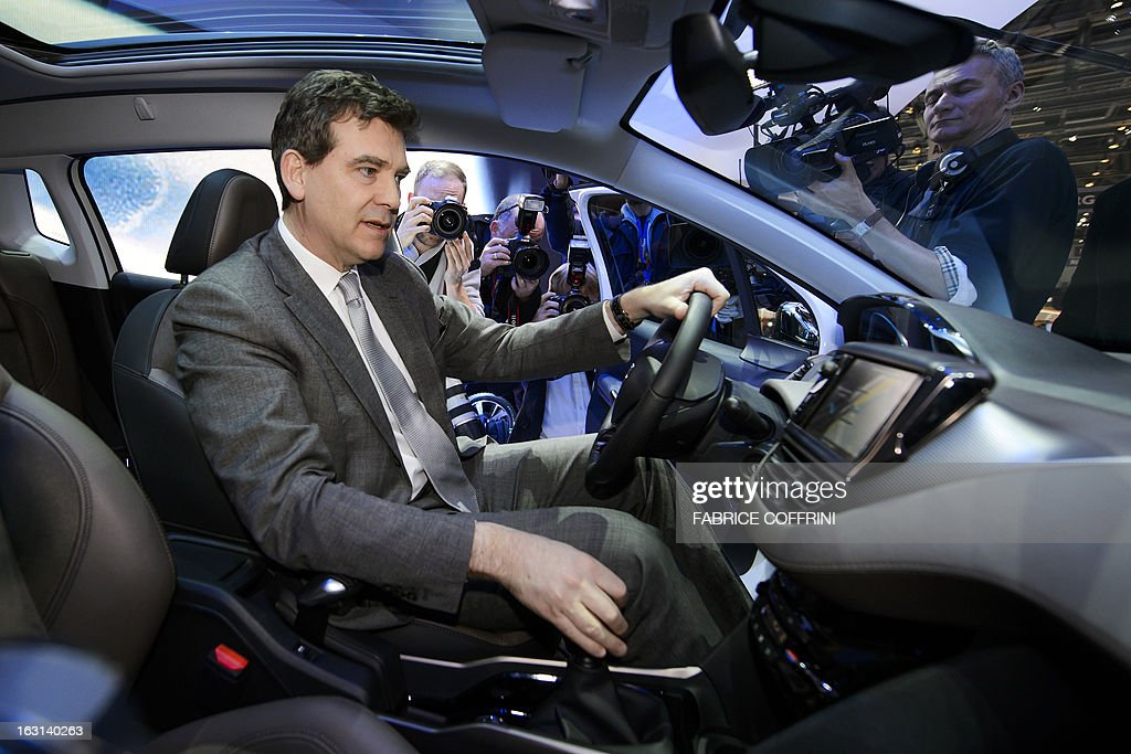 French Minister for Industrial Recovery Arnaud Montebourg is seen inside a new Peugeot 2008 presented in World Premiere during his visit to the 83rd Geneva Motor Show on March 5, 2013 in Geneva. The Geneva International Motor Show opened its doors to the press under a dark cloud, with no sign of a speedy rebound in sight for the troubled European market. The event, which is considered one of the most important car shows of the year, will again be heavily marked by the crisis in Europe after an already catastrophic year in 2012. AFP PHOTO / FABRICE COFFRINI