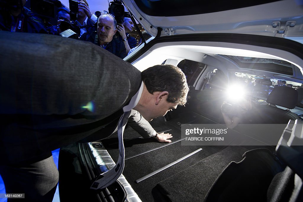 French Minister for Industrial Recovery Arnaud Montebourg looks inside the trunk of a new Peugeot 2008 presented in World Premiere during his visit to the 83rd Geneva Motor Show on March 5, 2013 in Geneva. The Geneva International Motor Show opened its doors to the press under a dark cloud, with no sign of a speedy rebound in sight for the troubled European market. The event, which is considered one of the most important car shows of the year, will again be heavily marked by the crisis in Europe after an already catastrophic year in 2012. AFP PHOTO / FABRICE COFFRINI