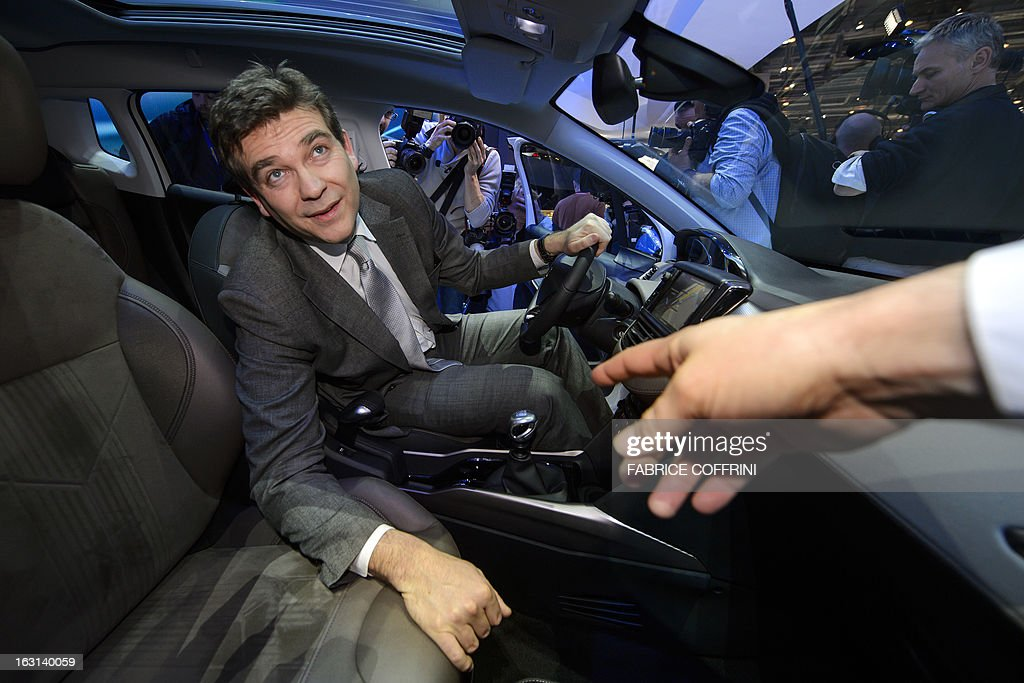 French Minister for Industrial Recovery Arnaud Montebourg receives information inside a new Peugeot 2008 presented in World Premiere during his visit to the 83rd Geneva Motor Show on March 5, 2013 in Geneva. The Geneva International Motor Show opened its doors to the press today under a dark cloud, with no sign of a speedy rebound in sight for the troubled European market. AFP PHOTO / FABRICE COFFRINI