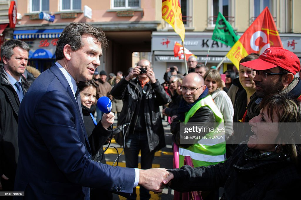 French Minister for Industrial Renewal and Food Industry Arnaud Montebourg (L) shakes hands with members of French unions during a visit in Belfort, on March 22, 2013.