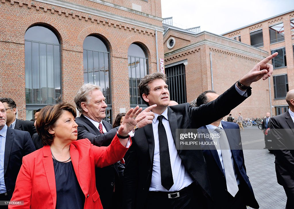 French minister for Industrial Renewal Arnaud Montebourg (C), flanked by Lille's socialist mayor Martine Aubry (L) and IBM France's president Alain Benichou (Back-R), gestures as he arrives at Lille's technology hub Euratechnologies, northern France, on June 24, 2013 to announce the opening of a new IBM service center. AFP PHOTO / PHILIPPE HUGUEN