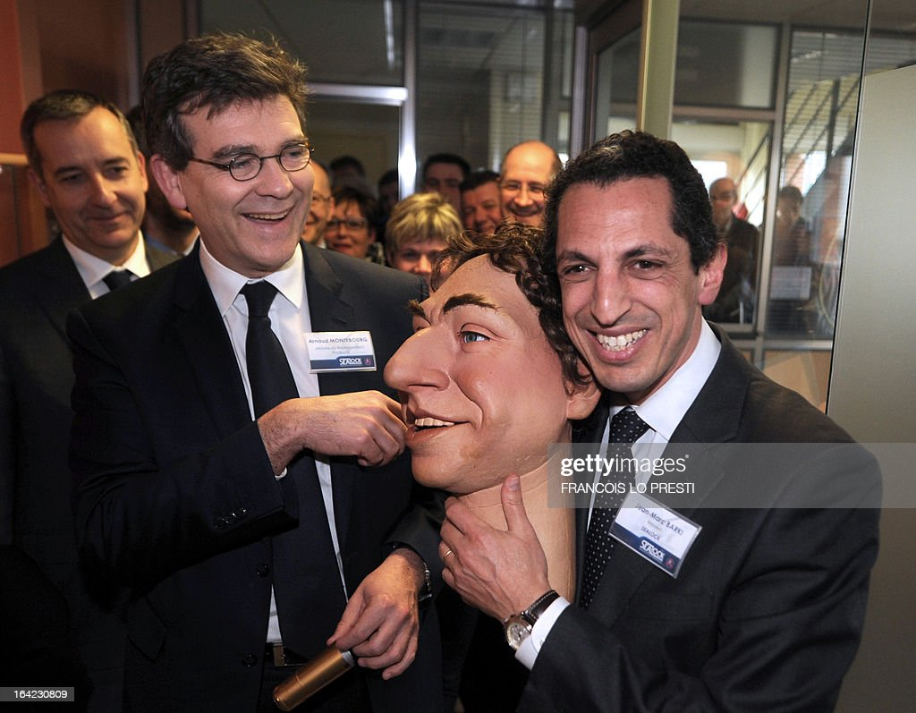 French Minister for Industrial Renewal Arnaud Montebourg (L) reacts beside Sealock head Jean-Marc Barki (R) as he holds a rubber latex puppet during his visit to the plant of industrial glue manufacturer Sealock in Sallaumines, northern France on March 21, 2013, as part of the 3rd edition of the 'Semaine de l'Industrie' (The Week for Industry).