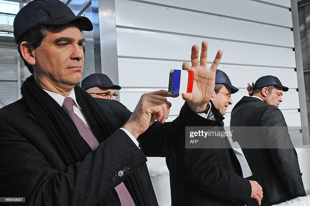 French minister for Industrial renewal Arnaud Montebourg takes a picture with his smartphone bearing the French flag during his visit of the Airbus A380 assembly plant on January 25, 2013 in Colomiers. AFP PHOTO/REMY GABALDA