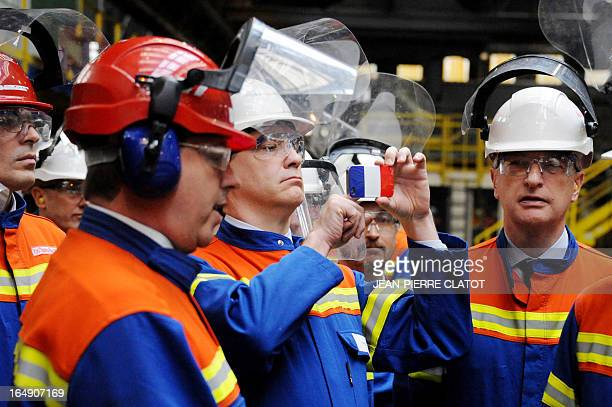 French Minister for Industrial Renewal Arnaud Montebourg takes a picture with his mobile phone during a visit at the Rio Tinto Alcan factory on March...