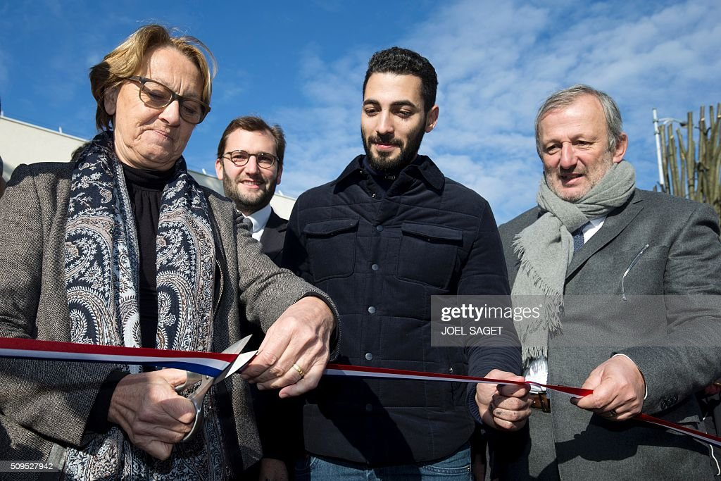 French minister for Public services Marylise Lebranchu (L), French street artist Combo (C) and Sarcelles Mayor Francois Pupponi (R) take part in the inauguration of the fresco '#CoexistSarcelles' on February 11, 2016 in Sarcelles, northern suburb of Paris. / AFP / JOEL SAGET