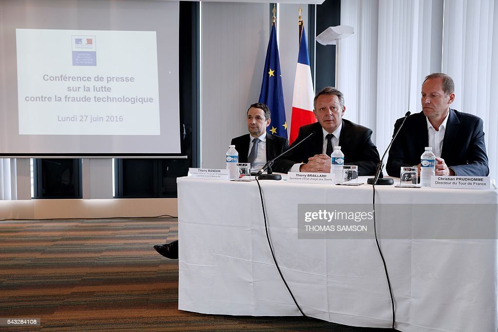 French Minister for Sports Thierry Braillard (C), flanked by French Minister for Higher Education and Research Thierry Mandon (L) and Tour de France race director Christian Prudhomme (R), speaks during a press conference on mechanical fraud, in Paris, on June 27, 2016. Thermal cameras will be used in this year's Tour de France to fight against motor cheats, French Minister of State for Sport Thierry Braillard announced on Monday. The cameras, which can detect a motor in a bicycle, have been developed by the Atomic Energy Commission (CEA) at the request of the French government. SAMSON