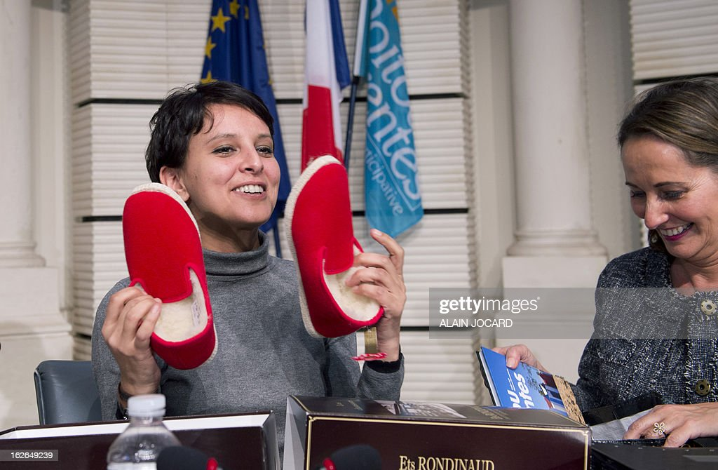 French Minister for Women's Rights and Government Spokeperson, Najat Vallaud-Belkacem (L) shows slippers she received by French region Poitou-Charentes president Segolene Royal (R) on February 25, 2013 in Vouneuil-sous-Biard near Poitiers during a debate on women entrepreneurship.