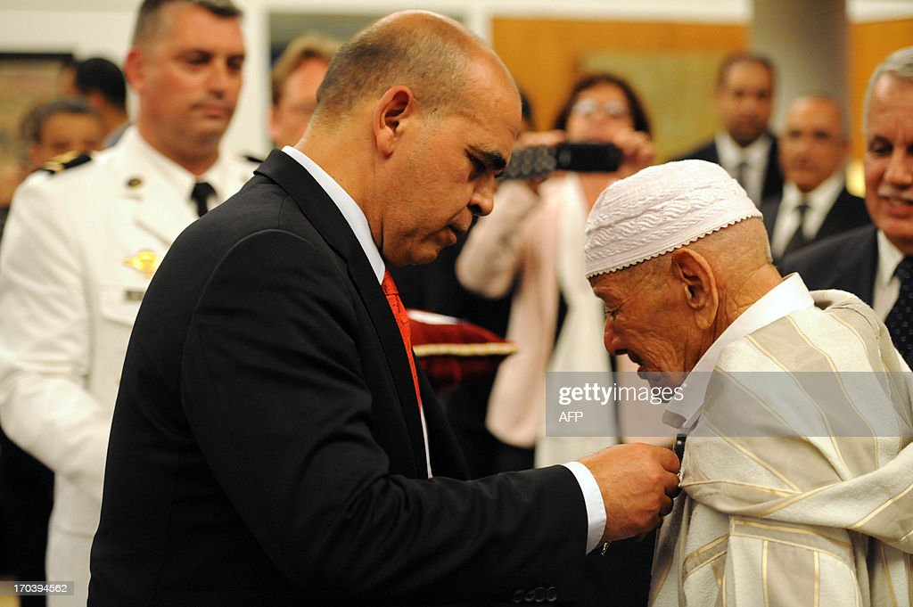 French Minister in charge of Veteran Affairs Kader Arif (L) decorates Moroccan veterans, who fought for France during World War II and Indochina war, during a ceremony at the French embassy in which they are being decorated for their bravery on June 12, 2013 in Rabat.