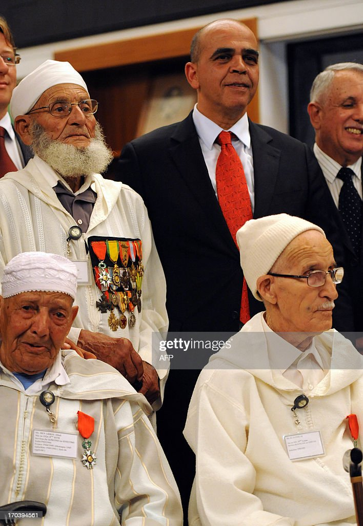 French Minister in charge of Veteran Affairs Kader Arif (2nd R) poses for a picture with Moroccan veterans, who fought for France during World War II and Indochina war, during a ceremony at the French embassy in which they are being decorated for their bravery on June 12, 2013 in Rabat.