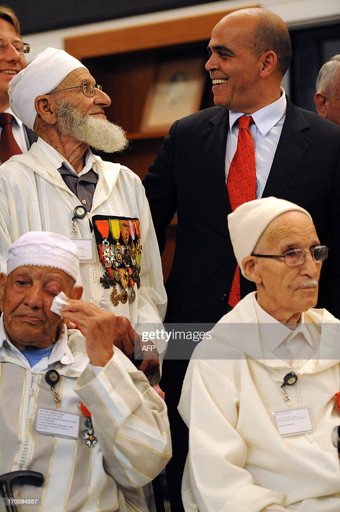French Minister in charge of Veteran Affairs Kader Arif talks to Moroccan veterans, who fought for France during World War II and Indochina war, during a ceremony at the French embassy in which they are being decorated for their bravery on June 12, 2013 in Rabat.