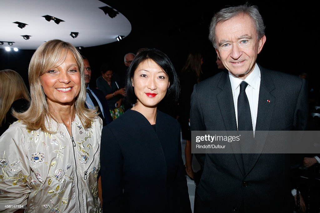 French minister of Culture and Communication <a gi-track='captionPersonalityLinkClicked' href=/galleries/search?phrase=Fleur+Pellerin&family=editorial&specificpeople=8784076 ng-click='$event.stopPropagation()'>Fleur Pellerin</a> standing between Owner of LVMH Luxury Group <a gi-track='captionPersonalityLinkClicked' href=/galleries/search?phrase=Bernard+Arnault&family=editorial&specificpeople=214118 ng-click='$event.stopPropagation()'>Bernard Arnault</a> and his wife <a gi-track='captionPersonalityLinkClicked' href=/galleries/search?phrase=Helene+Arnault&family=editorial&specificpeople=718530 ng-click='$event.stopPropagation()'>Helene Arnault</a> attend the Christian Dior show as part of the Paris Fashion Week Womenswear Spring/Summer 2015 on September 26, 2014 in Paris, France.