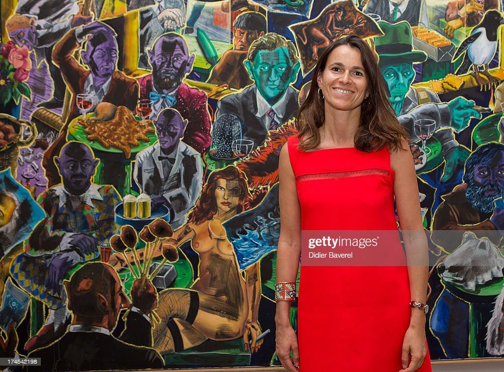 French Minister Of Culture Aurelie Filippetti poses in front of a painting of Jorg Immendorff ' Cafe de Flore' at Fondation Maeght exhibition as part of Festival Des Nuits du Sud at Fondation Maeght on July 27, 2013 in Saint-Paul-De-Vence, France.